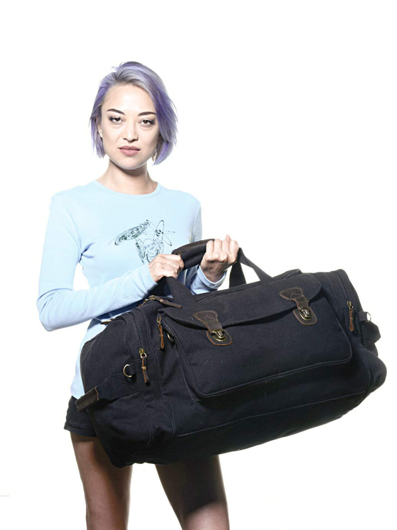 Kalia holding a black travel bag from carrying handles